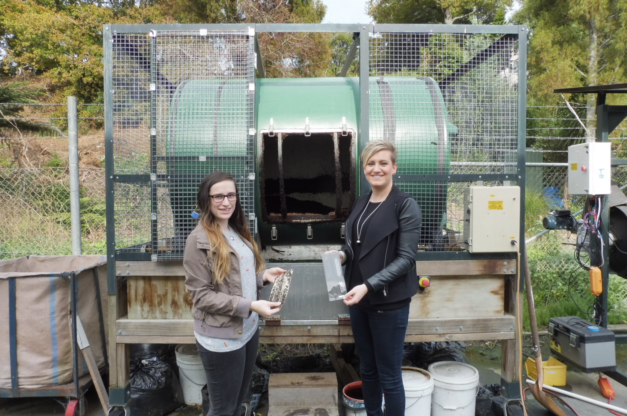 Convex Lab Assistant Courtney-Ruth Gill (left) comparing the Econic bag that has been in the composter for several weeks with the non-composted Econic bag that Convex Lab Manager Crystal Pope is holding.
